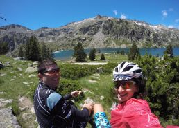 Two cyclists sitting by the shore of Lac d'aumar on the route de lacs cycling climb in the French Pyrenees.