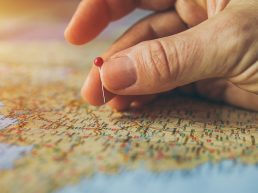 ingers holding a pin over a map in France choosing where to go