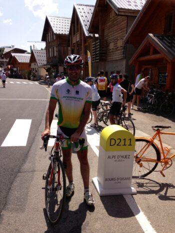 A cyclist standing at the Alpe d'Huez summit sign in the French Alps