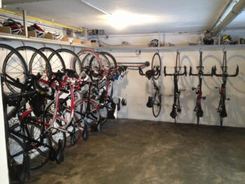 several bikes hanging from hooks at a cycling lodge garage