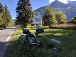 Bike leaning against an indicator sign for the Col des Montets