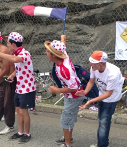 Tour de france fans cheering riders on the side of the road