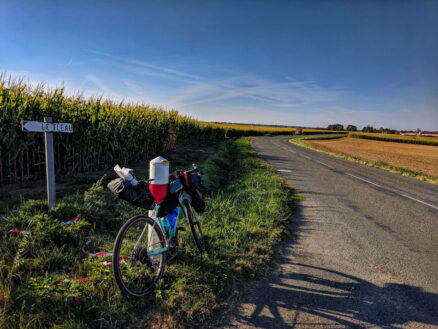 A bike with touring packs attached leaning on a post beside a road in France