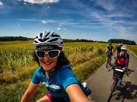 A group of cyclists riding past sunflowers in France