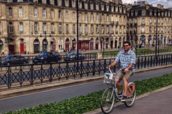 A man cycling in Bordeaux on a hire bike