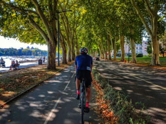 A cyclist riding on a tree lined bike path in Lake Annecy France