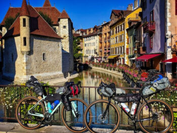 Two bikes with touring packs leaning agains a bridge railing in Annecy