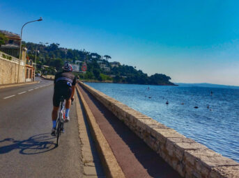 A cyclist riding along the road on the French Mediterranean with the sea by their side