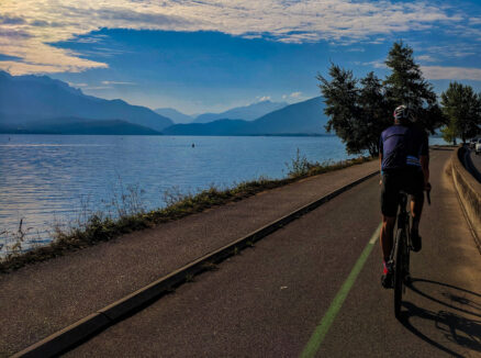 A cyclist riding next to Lake Annecy on a cycle path