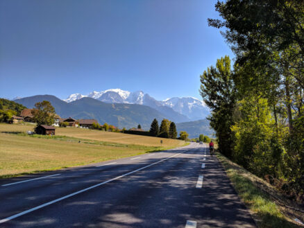 A cyclist on the road with the snow capped mountains of the French Alps in the bacground.
