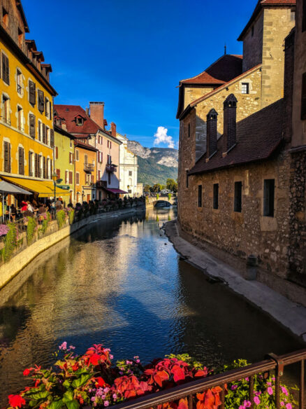 Looking down the canals in Annecy with flowers in the foreground