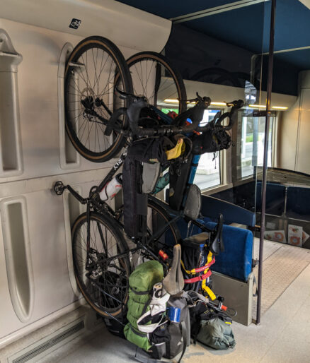 Two bikes hanging on racks on a French train