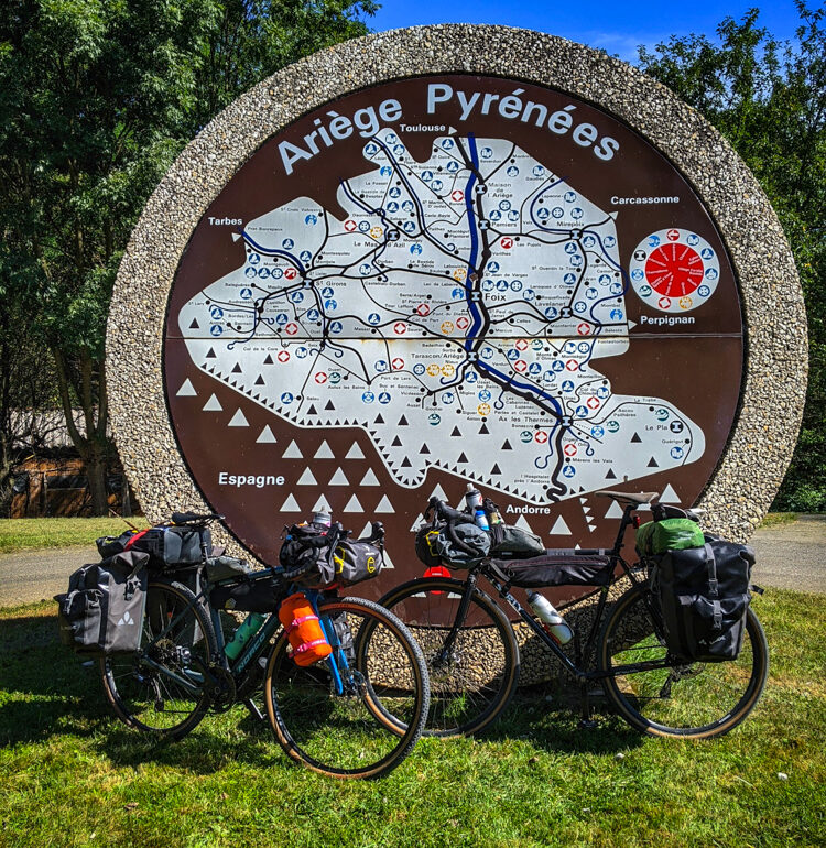 Two bikes in front of the Ariege Pyrenees sign