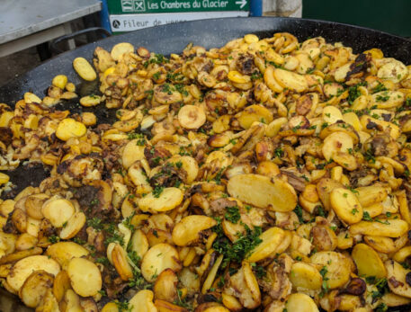 A dish of roasted potato slices with bacon and mushrooms at the food markets in Sarlat la Caneda France
