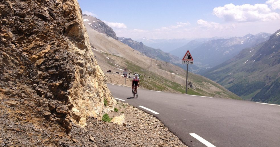 Cycling in the French Alps. A women cycling to the summit of Col du Galibier