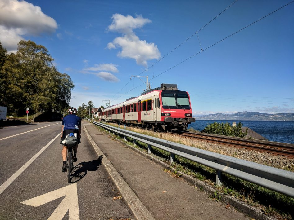 Male cyclist riding along Lac leman with a train travelling in the opposite direction