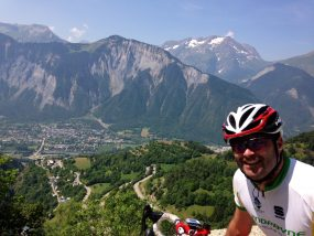 Male cyclist on the climb of Alpe d'Huez in the French alps with the hairpins on the road