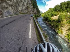Cyclists riding by a river on the route de lacs route. A lesser known climb of the French Pyrenees.