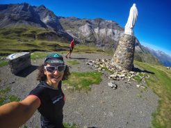 Two cyclists at the large statue of Mary at the summi of Cirque de Troumouse in the Pyrenees
