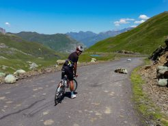 Cyclist on the Col de Tentes climb with sheep on the road