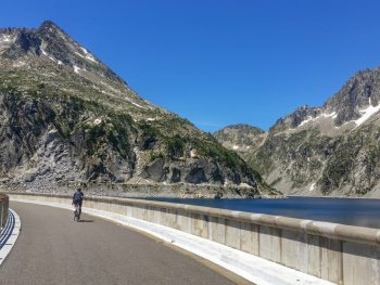 Cyclist riding across the dam wall at the top of Lac de Cap de Long. A lesser known climb in the French Pyrenees