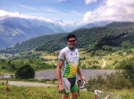 cyclist standing at the summit of col du couraduque. Large Pyrenees mountains in the background