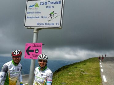 Two cyclists having their photo taken at the Col de Tramassel summit 1635m