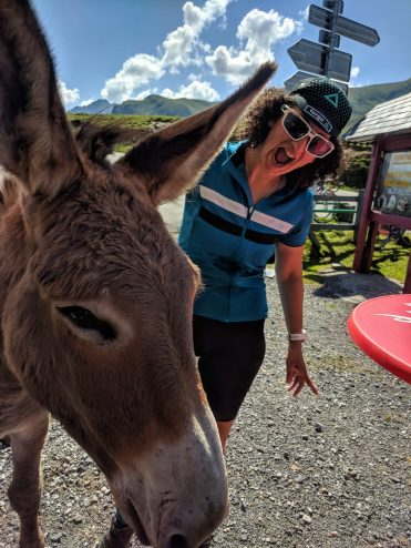 A female cyclists having photo taken with a donkey at the summit of the col du Soulor in the Pyrenees