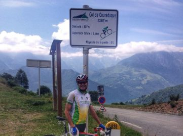 Male cyclist at the summit sign of Col du Couraduque in the French Pyrenees