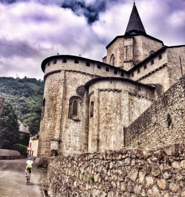 cyclist riding past the Abbey of Saint Savin in the French Pyrenees
