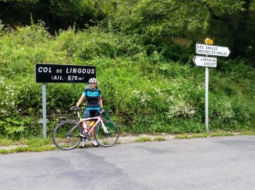 Female cyclist standing at the summit sign of the Col de Lingous in the French Pyrenees