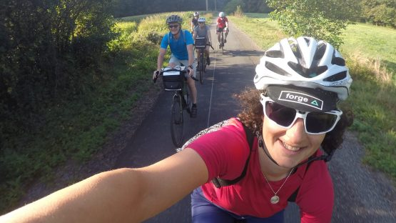 five people riding bikes along the Lourdes rail trail greenway in the French Pyrenees.