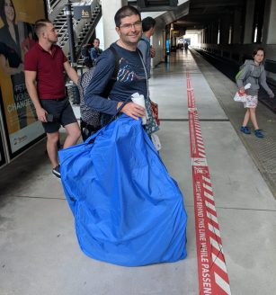 Man waiting on train platform with bicycle packed in a Rinko bag