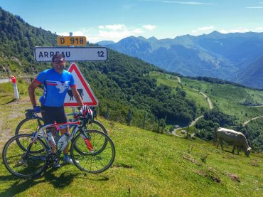 Cyclist at the summit of Col d'Aspin. Views of the Pyrenees mountains in the background.