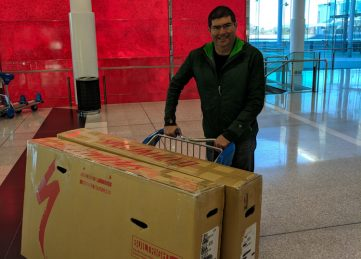 Wheeling a trolley through the airport with bikes packed in boxes for a trip to France
