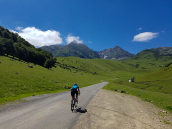 A cyclists on the road surrounded by green fields and mountains on the Hourquette d'Ancizan in France