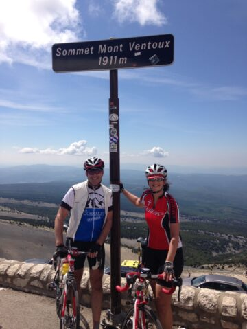 Two cyclists in front of the Mont Ventoux summit sign