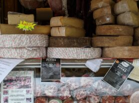 wheels of cheese and smallgoods for sale at a Chamonix market stall