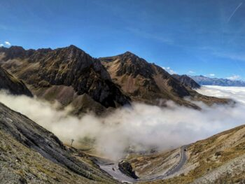 Col du Tourmalet summit panorama. Fog lying in the lower valley with the road the summit visible below.