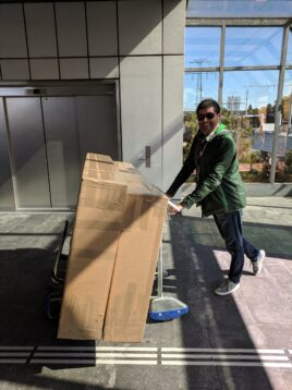 Man taking bikes on plane in cardboard boxes