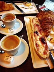 french breakfast, coffee, croissant and baguette with butter and strawberry jam